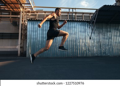 Handsome young man running in ndustrial building background.  runner, jogger, fitness activity