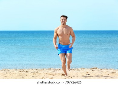 Handsome young man running on sea beach