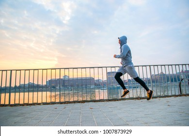 A handsome young man running in the sunset next to a fence on the riverside