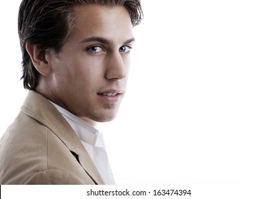Handsome young man with a sensual expression standing sideways looking at the camera, head and shoulders portrait on white