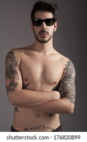handsome young man with several tattoes posing topless for camera