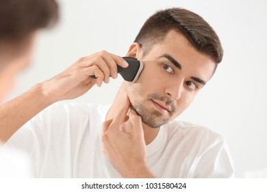 Handsome young man shaving in bathroom