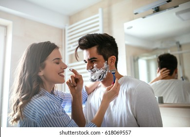 A handsome young man shaving in the bathroom.