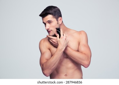 Handsome young man shaving with electric shaver over gray background