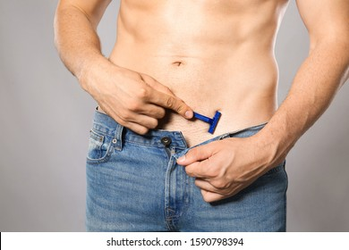 Handsome young man shaving his body on grey background, closeup