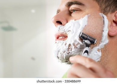Handsome young man is shaving his face