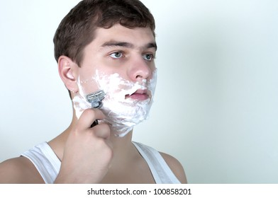 A handsome young man shaving in the morning