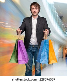 Handsome young man with shopping bags in shopping mall