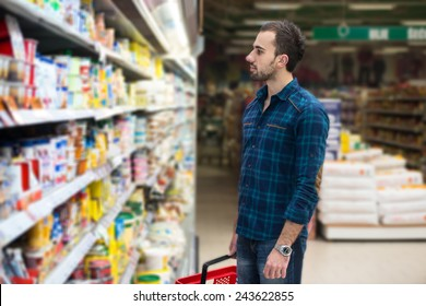 Handsome Young Man Shopping For Fruits And Vegetables In Produce Department Of A Grocery Store - Supermarket - Shallow Deep Of Field
