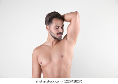 Handsome young man showing armpit on white background. Using deodorant