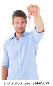 Handsome young man showing new house key on white background