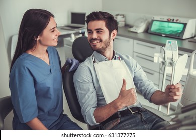 Handsome young man is showing Ok sign and talking to beautiful female dentist while sitting in chair at the dentist