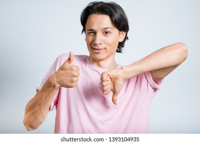 handsome young man showing thumbs up and down, hipster, studio photo on gray background