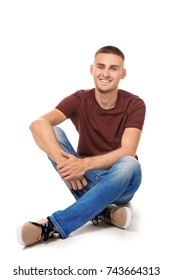 Handsome young man sitting against white background