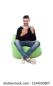Handsome young man sitting on a bean bag, holding his phone texting someone and he is reading a new news so he is very happy, isolated on white background