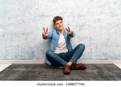 Handsome young man sitting on the floor smiling and showing victory sign