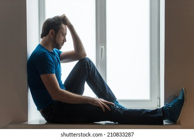 Handsome young man sitting on windowsill. Guy holding head and wearing blue shirt and jeans