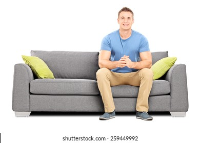 Handsome young man sitting on a modern sofa isolated on white background