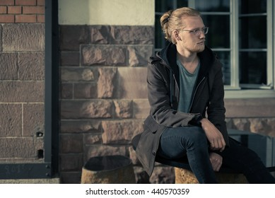 Handsome Young Man Sitting on Stone Furniture