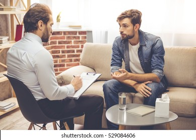 Handsome young man is sitting on couch and talking to the psychologist while doctor is making notes