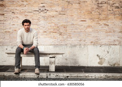 Handsome young man sitting on marble bench with bricks background. A beautiful and young boy sat on a marble bench. Behind him a large, old brick wall. Beside him, a large copy space.