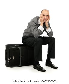 Handsome young man sitting on his luggage