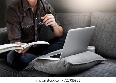Handsome Young Man Sitting on the Living Room Couch, Casual young man reading documents on sofa at home.