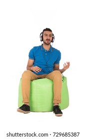 Handsome young man sitting on green chair and listening to music, guy wearing blue t-shirt and beige pants, isolated on white background