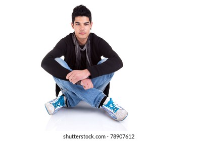 Handsome young man, sitting on the floor, relaxed and confident. Studio shot over white background.