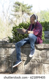Handsome young man sitting in the park , use tablet and listens to music. Selective focus and small depth of field.