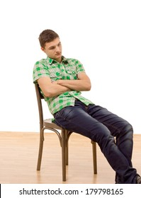 Handsome young man sitting slumped in a wooden chair with his arms folded staring down at the the ground with a thoughtful expression, isolated on white