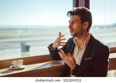 Handsome young man sitting at window in cafe while gesturing and talking.