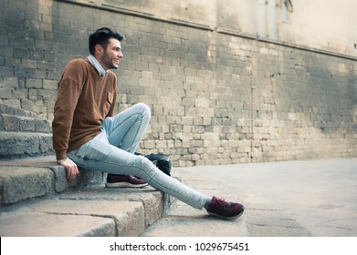 handsome young man sittion on a stair at the street
