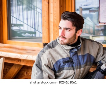 Handsome young man in skiing suit relaxing, sitting at table outside ski resort