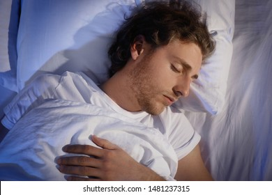 Handsome young man sleeping on pillow at night, top view. Bedtime