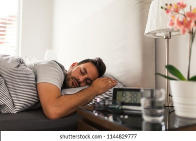 Handsome young man sleeping peacefully in his bedroom