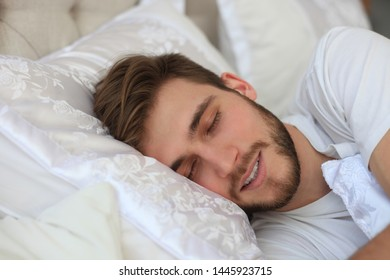 Handsome young man sleeping in white bedding.