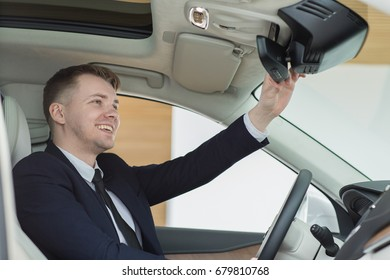 Handsome young man smiling adjusting rearview mirror sitting in new car at the dealership checking out interior of the automobile he is buying comfort luxury travel lifestyle people buyer consumerism