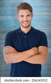 Handsome young man smiling with arms crossed against wooden planks