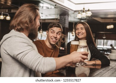 Handsome young man smiling happily, enjoying resting at the bar with his friends. Group of friends having drinks at the local beer pub. Two men and beautiful woman drinking beer. Celebration concept