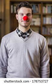 Handsome young man smiling with red clown nose, standing in a living room