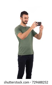 Handsome young man smiling and taking a photo, guy wearing green t-shirt and black pants, isolated on white background