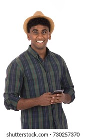Handsome young man smiling and using a cellphone, guy wearing caro shirt and beige hat, isolated on white background