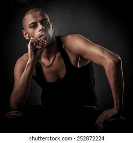 Handsome young man smokes cigarette in darkness - photography of unhealthy addiction