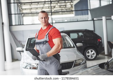 A handsome young man speaks at a car dealership, repairing a car in a workshop