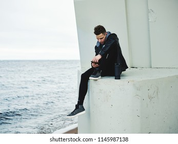 Handsome young man in sportswear sitting on ledge near sea and browsing smartphone during outdoor training