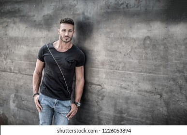 Handsome young man standing against concrete wall, looking at camera, wearing black t-shirt and jeans