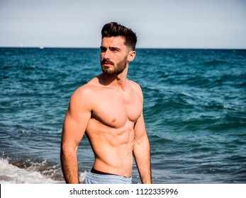 Handsome young man standing at a beach, relaxed, shirtless wearing boxer shorts