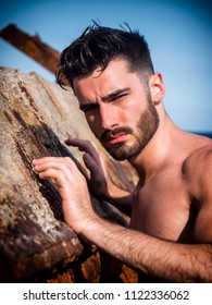 Handsome young man standing next to rusty metal structure, shirtless wearing boxer shorts, looking at camera
