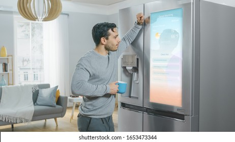 Handsome Young Man is Standing Next to a Refrigerator While Drinking His Morning Coffee. He is Checking a To Do List on a Smart Fridge at Home. Kitchen is Bright and Cozy.